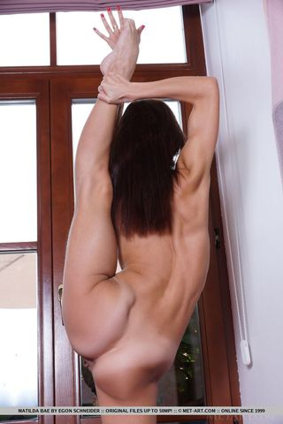 Гимнастка дома на полу задирает в шпагат ногу и напрягает влагалище