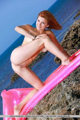 Рыжая на пляже на розовом надувном матрасе гладит сиськи и писечку