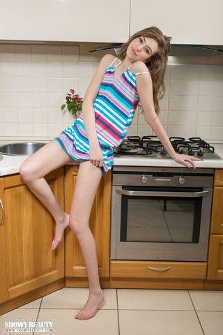 Худая девушка на кухне показывает на столе бритое влагалище