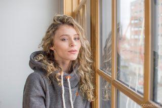 Блондинка с кудрявыми волосами стоит голая около окна и кайфует
