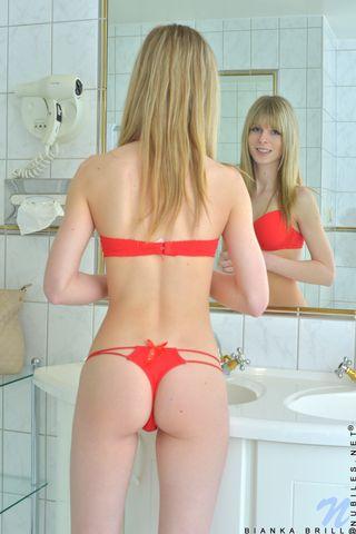 Блонда в серых туфлях садится на корточки и гладит напряженную пилотку