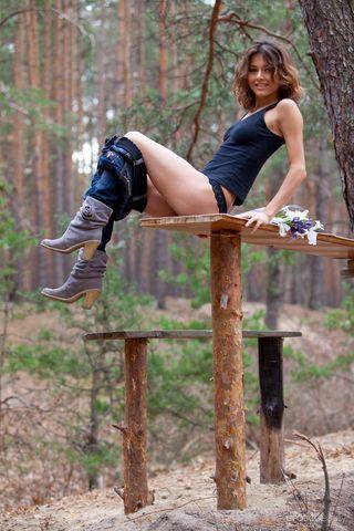 Модель в лесу на деревянном столе снимает нижнее белье и работает голышом