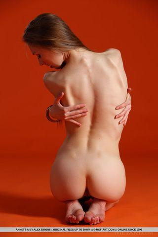 Стройная модель в студии на оранжевом фоне мастурбирует пилотку
