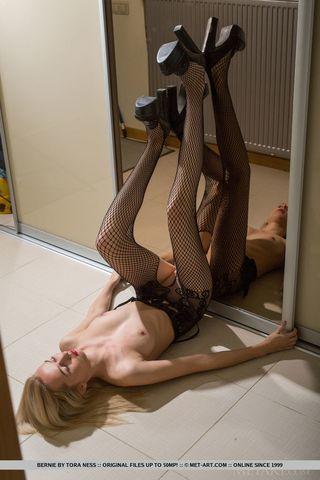 Блондинка в колготках рассматривает в зеркало бритое мягкое влагалище