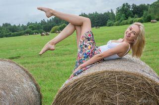 Блонда на стогу сена показывает в камеру бритую писечку