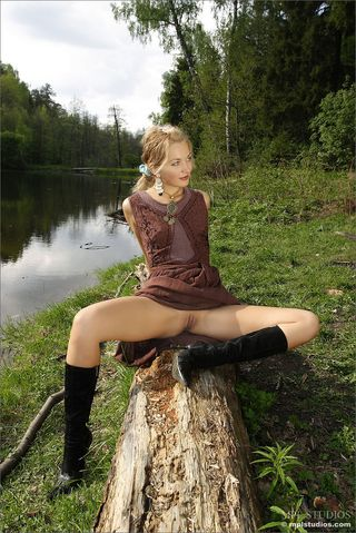 Девушка на каблуках позирует около реки на упавшем дереве нагишом
