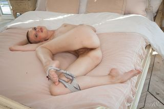 Бритоголовая девушка демонстрирует лохматку на спине в кровати